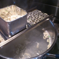 spaetzle maker over pot of hot water