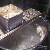 spaetzle maker over pot of hot water